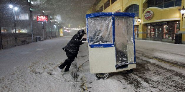 A man maneuvers his Push cart with passengers during a snowstorm early Saturday, Jan. 23, 2016, on the...