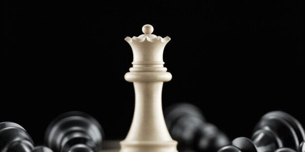 White queen chess piece surrounded by fallen black pawn chess