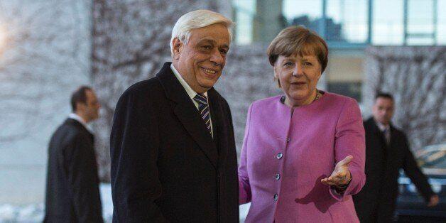 German Chancellor Angela Merkel (R) greets Greek President Prokopis Pavlopoulos prior to talks at the...