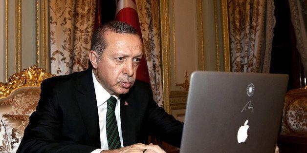 Turkey's President Recep Tayyip Erdogan checks to vote for photos produced in 2015 by semi-offcial Anadolu...