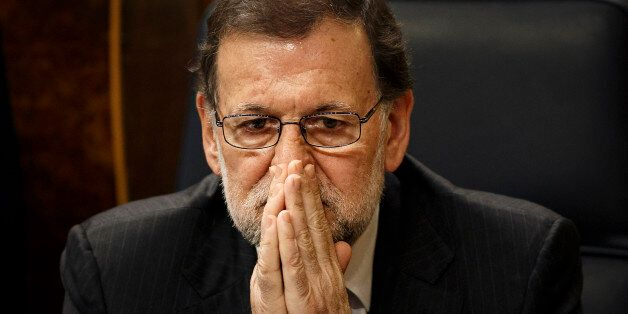 CORRECT THE TITLE OF RAJOY Spain's Acting Prime Minister Mariano Rajoy sits on his chair at the Spanish...