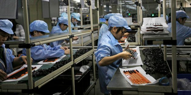 In this Aug. 21, 2015 photo, Chinese women work at Rapoo Technology factory in southern Chinese industrial...