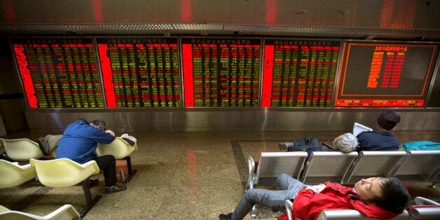 Chinese investors nap while monitoring stock prices at a brokerage house in Beijing, Friday, Dec. 4,...