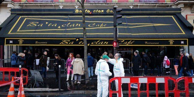 City workers clean the sidewalk and the street in front of the Bataclan concert hall in Paris on December...