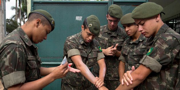 Army soldiers apply insect repellent as they prepare for a clean up operation against the Aedes aegypti...