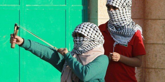 A Palestinian female protester uses a slingshot to throw stones towards Israeli security forces during...