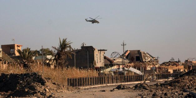 Iraqi military helicopter flies over destroyed houses as security forces clearing the Soufiya neighborhood...