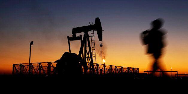 A boy walks by an oil pump at sunset Monday, Jan. 18, 2016, in the desert oil fields of Sakhir, Bahrain....