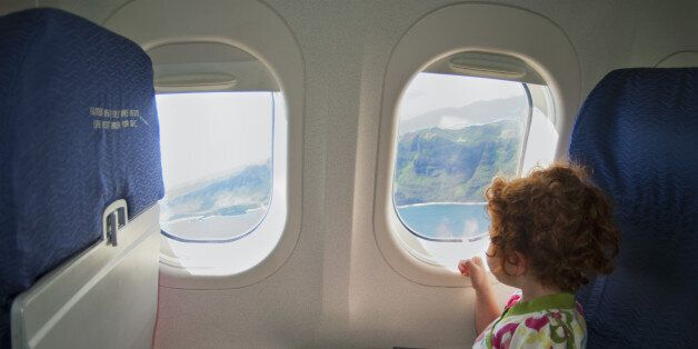 Little girl looking out an airplane window.