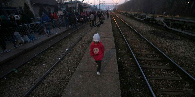 A migrant child walks along the side of railway tracks at the railway station in the southern Serbian...