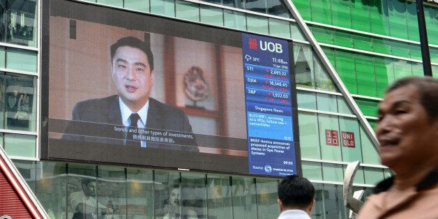 A big screen displays information on the stock index at the Raffles Place financial district in Singapore...