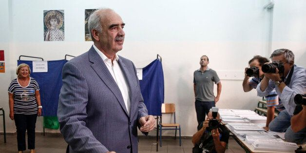 Evangelos Meimarakis, leader of the New Democracy Party of Greece, reacts as he places his voting slip...