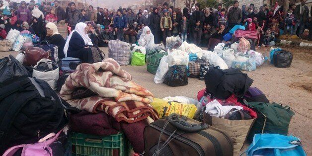 Syrians wait for the arrival of an aid convoy on January 11, 2016 in the besieged town of Madaya as part...