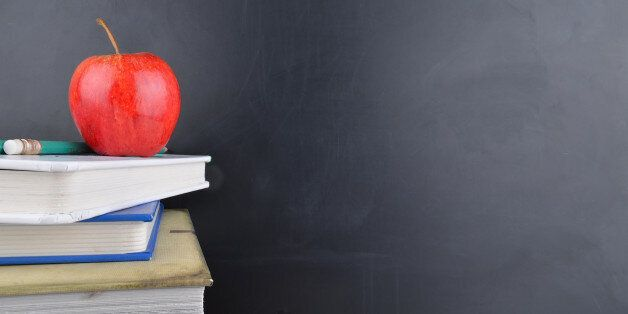 A classroom with a red apple, books and a blackboard with handwriting in white chalk on the