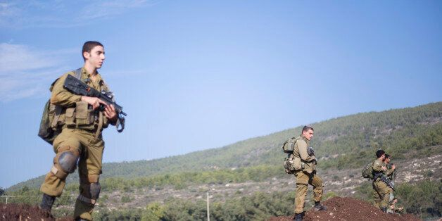 Israeli soldiers of the Golani brigade search for rockets fired from Lebanon after they landed in northern...