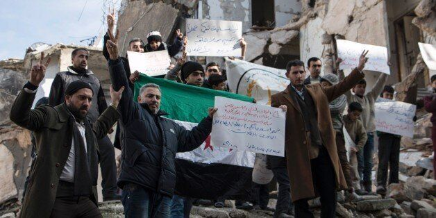 Syrians hold banners amid rubble during a demonstration on January 10, 2016 in the northern city of Aleppo...