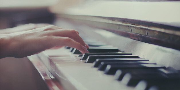 Female hands playing piano, close