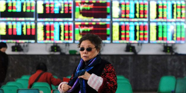 An investor makes her way in front of screens showing stock market movements in a stock firm in Wuhan,...