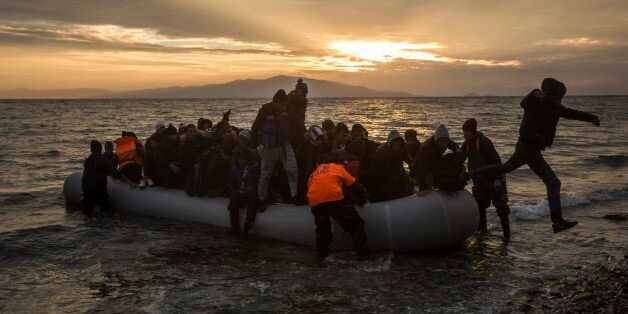 Refugees and migrants disembark on a beach after crossing a part of the Aegean sea from the Turkey's...