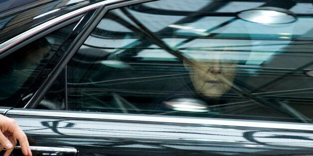 German Chancellor Angela Merkel looks out of her car window as she arrives for an EU summit at the EU...
