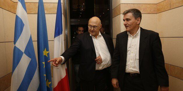 French Finance minister Michel Sapin (C) shows the Greek flag as he welcomes his Greek counterpart Euclide...
