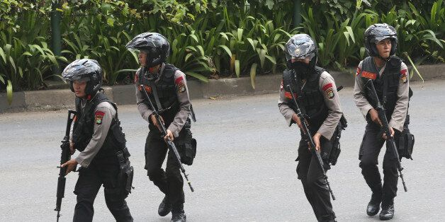 Police officers rush to take their position at the site of an attack in Jakarta, Indonesia Thursday,...