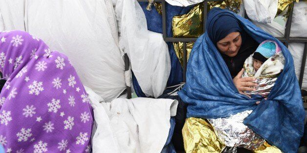 Migrant woman with a baby protects themselfes from the cold as she waits to cross the Austrian-German...