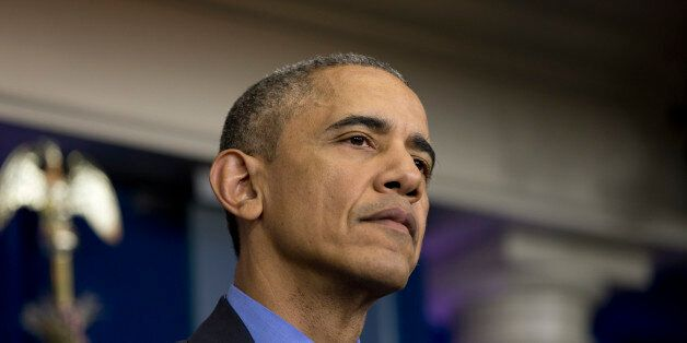 President Barack Obama pauses to listen to question during a news conference in the briefing room at...