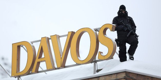 An armed police officer stands on the snow-covered rooftop of the Hotel Davos and looks out over the...