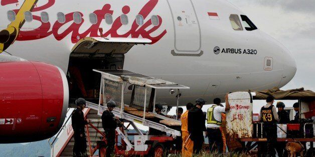 Indonesian bomb squad personnel use sniffer-dogs to inspect luggae on a Batik Air domestic airlines plane...