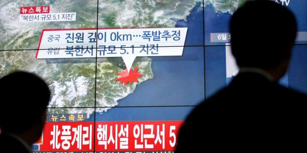 People walk by a screen showing the news reporting about an earthquake near North Korea's nuclear facility,...