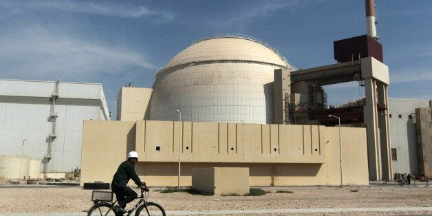 FILE - In this Oct. 26, 2010 file photo, a worker rides a bicycle in front of the reactor building of...
