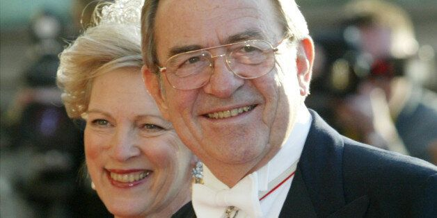 Former King Constantine of Greece and his wife Queen Anne Marie pass press photographers on their way...