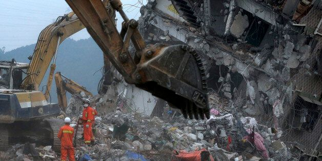 Rescuers search for potential survivors near a damaged building following a landslide at an industrial...