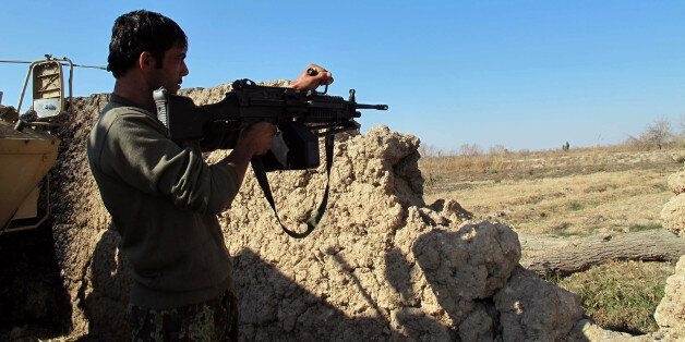 An Afghan National Army (ANA) soldier keeps watch during an ongoing battle with Taliban militants in...
