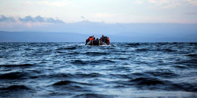 Migrants and refugees approach on a dinghy the northeastern Greek island of Lesbos from the Turkish coast,...