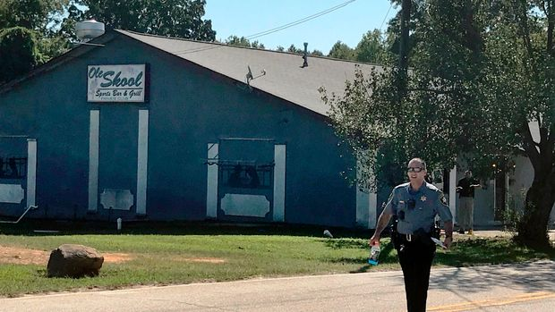 A Lancaster County Sheriff's deputy walks around the Old Skool Sports Bar and Grill, the scene of a shooting early in the morning, north of Lancaster, S.C. on Saturday, Sept. 21, 2019.  Lancaster County Sherriff's Office said in a statement that the agency was investigating a fatal shooting that also injured several people.  (Jessica Holdman/The Post And Courier via AP)