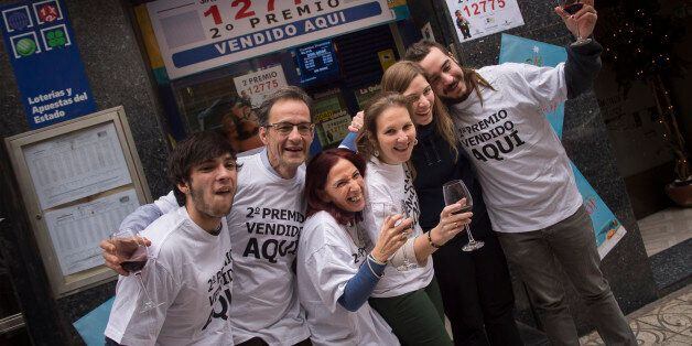 Cristina Ruiz, third left, 53, celebrates in front of a lottery office with red wine beside others owners...
