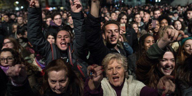BARCELONA, SPAIN - DECEMBER 20: Podemos (We Can) supporters cheer at the first exit poll results on December...