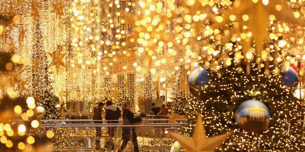 BERLIN, GERMANY - DECEMBER 22: Shoppers walk among Christmas lights at a shopping mall two days before...