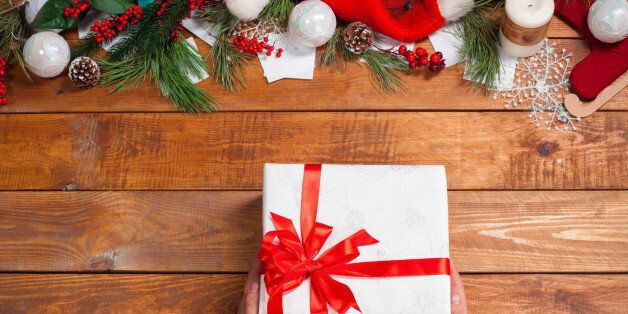 The wooden table with Christmas decorations with hands with gift. Christmas