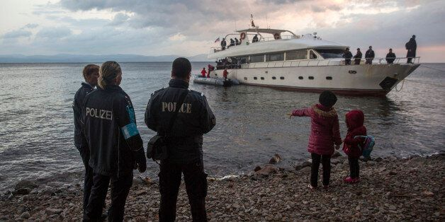 Frontex security personnel watch refugees and migrants disembarking from a yacht on the Greek island...