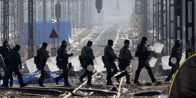 Greek riot police officers walk across railway tracks at Idomeni railway station in northern Greece on...