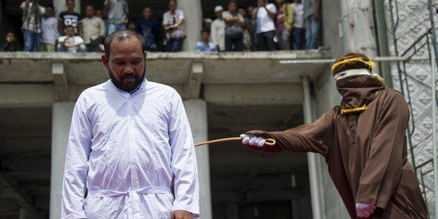 An Indonesian Sharia police whips a man during a public caning ceremony outside a mosque in Banda Aceh,...
