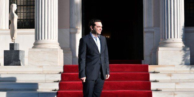 Greek Prime Minister Alexis Tsipras waits for the arrival of Egyptian President Abdel Fattah al-Sissi...