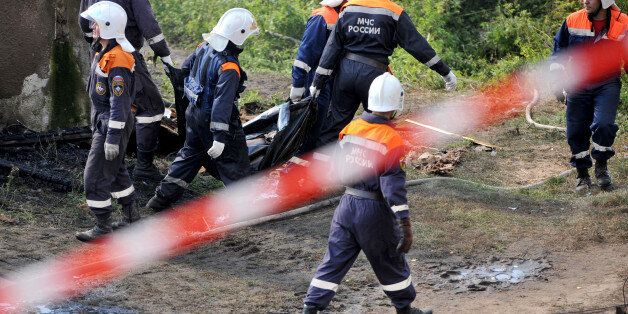 Rescuers carry a body bag with a victim of a fire near the charring remains of a burned out psychiatric...