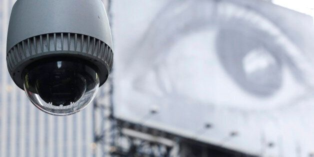 A security camera is mounted on the side of a building overlooking an intersection in midtown Manhattan,...