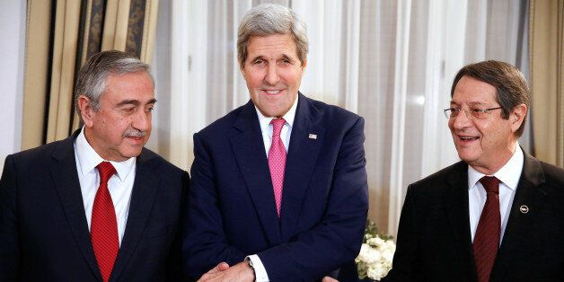 US Secretary of State John Kerry (C) shakes the hands of Cypriot President Nicos Anastasiades (R) and...