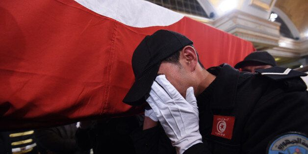 A Tunisian policeman mourns as he carries the coffin of a member of the presidential guards, who was...