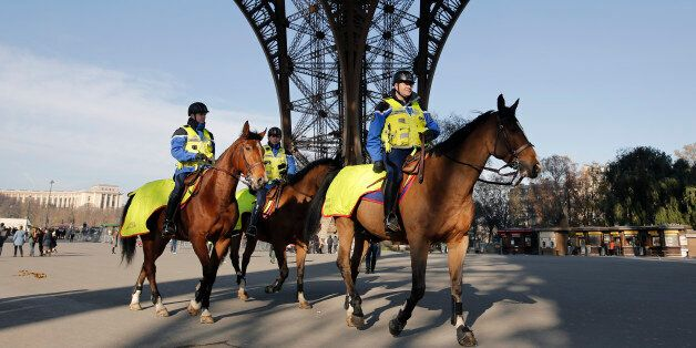 Mounted police officers patrol under the Eiffel Tower in Paris, Monday Nov. 23, 2015. French President...